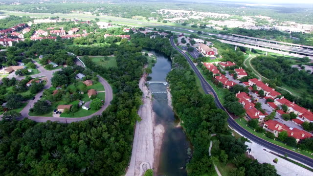 aerial: georgetown texas aerial fly by over san gabriel river apartments hill country town - georgetown texas stock videos & royalty-free footage