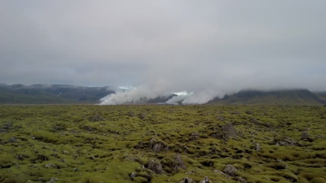 Aerial: Geothermal Pond Steaming in Wide Plain with Mossy Rocks on a Cloudy Day, Vik, Iceland