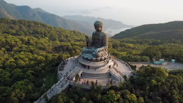 aerial: giant statue of buddha and mountains behind on lantau island, hong kong - buddha stock-videos und b-roll-filmmaterial