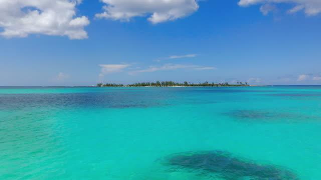 aerial: gliding across serene tropical water towards deserted island on a sunny day - nassau, bahamas - sunny点の映像素材/bロール