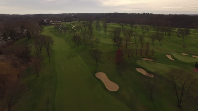 Aerial gliding along golf course toward clubhouse on fall day