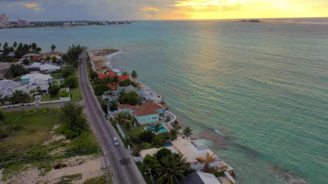aerial: golden sunset behind clouds and three people swimming near waterfront homes in tropical town - nassau, bahamas - beach house stock videos & royalty-free footage