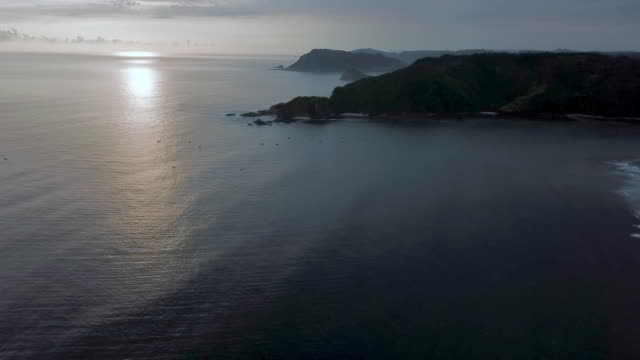 aerial: gorgeous bali sea, coastal hills and island on misty horizon in lombok, bali - bali stock videos & royalty-free footage