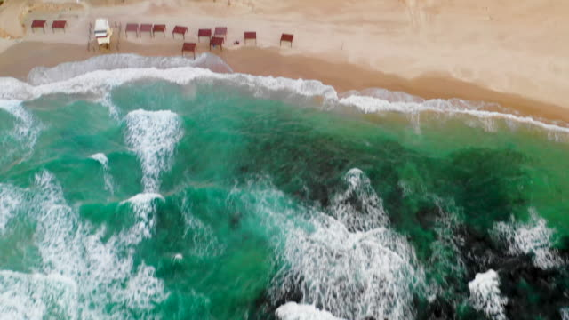 aerial: gorgeous blue ocean with waves crashing on beach in caesarea, israel - caesarea stock videos & royalty-free footage