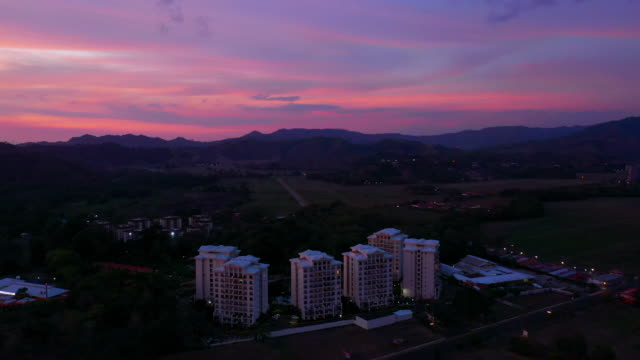 aerial: gorgeous sunset sky over mountains and six white hotels standing tall in city - jaco, costa rica - nummer 6 bildbanksvideor och videomaterial från bakom kulisserna