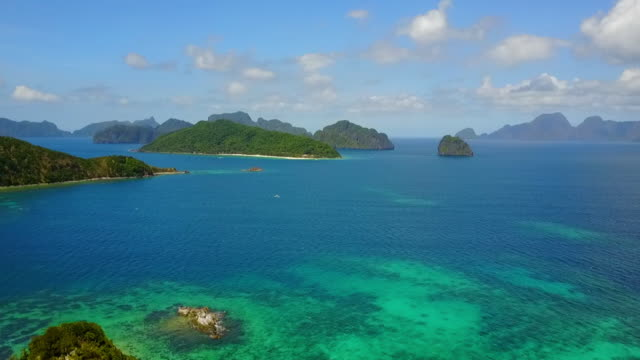 aerial: green islands among blue ocean in palawan, philippines - anchored stock videos & royalty-free footage