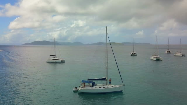 aerial: group of boats anchored in tropical ocean and another boat drives off in st. croix, us virgin islands - anchored stock videos & royalty-free footage