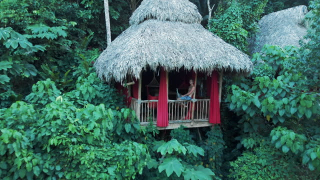 aerial: handsome young man sitting on balcony balustrade of lovely tree house - shack stock videos & royalty-free footage