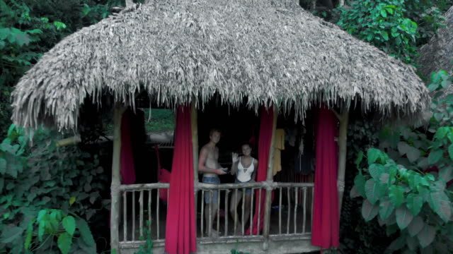 vídeos de stock, filmes e b-roll de aerial: happy young couple on balcony of charming tree house in the jungle - treehouse