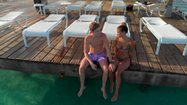 vídeos de stock, filmes e b-roll de aerial: happy young couple on wooden dock with sunbeds on crystal clear water - cadeira de praia
