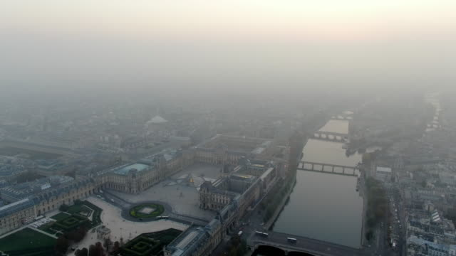 aerial: hazy paris cityscape with the river seine and the louvre palace, france - smog stock videos & royalty-free footage