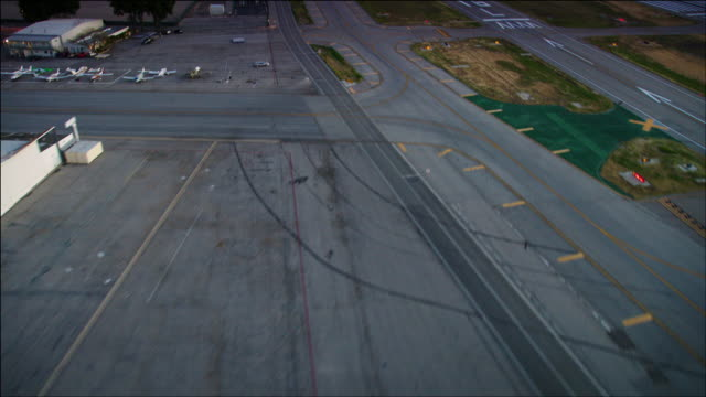 aerial helicopter pov, approach to landing on taxiway b at van nuys airport, in the san fernando valley, los angeles, ca, early evening. - taxiway stock videos & royalty-free footage