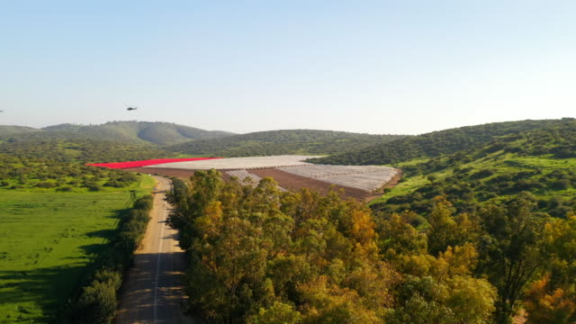 aerial: helicopter flying over farmland in rural lachish - israele video stock e b–roll