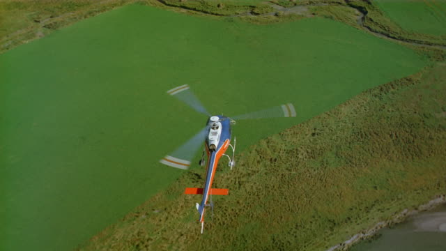 aerial helicopter flying over mud flats to verdant fields / new zealand - helicopter rotors点の映像素材/bロール