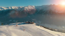 Aerial helicopter shot of calm rural mountain landscape, snow-covered mountain peaks and ski resort landscape at the Austrian Alps on a sunny afternoon day