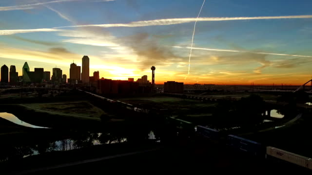 Aerial High above RailRoad Tracks over Trinity River Downtown Dallas Texas dramatic Colorful Sunrise Reunion Tower
