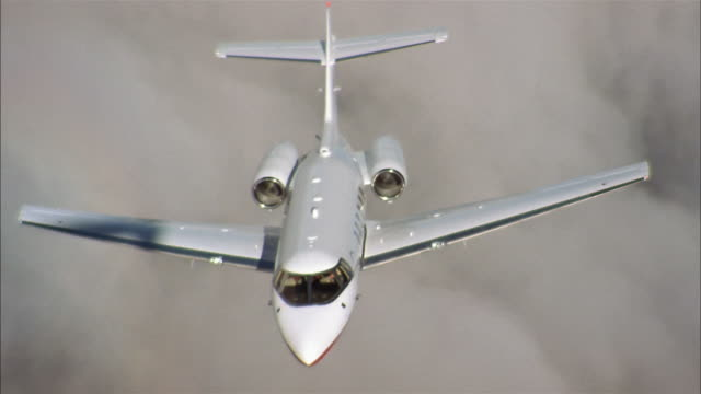 aerial high angle medium shot private jet in flight above cloud layer - private jet stock videos & royalty-free footage