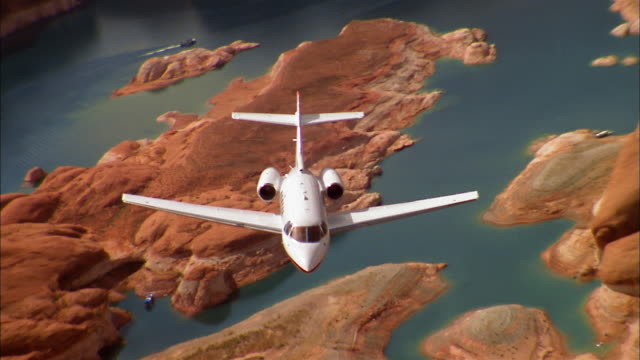 vidéos et rushes de aerial high angle private jet flying over grand canyon / arizona - colorado