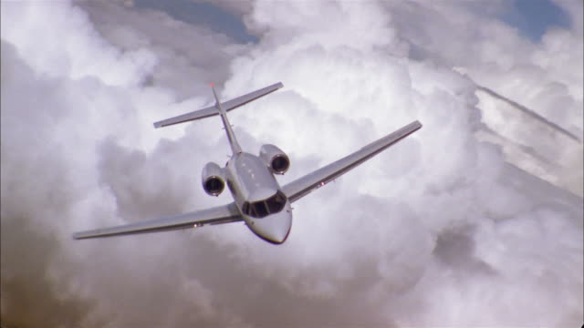 aerial high angle private jet in flight banking in air through clouds - air to air shot stock videos and b-roll footage
