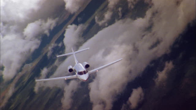 aerial high angle private jet in flight banking through clouds - air to air shot stock videos and b-roll footage