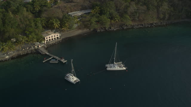 aerial high angle view of catamarans in ocean near dock / wallilabou bay, st. vincent, saint vincent and the grenadines - coastal feature stock videos & royalty-free footage