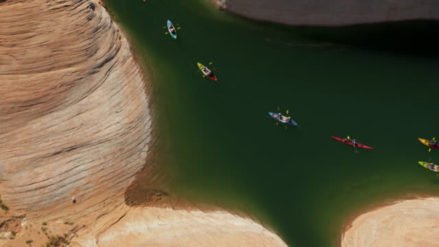 aerial high angle view of distant people paddling kayaks in remote lake / glen canyon, arizona, united states - canyon stock-videos und b-roll-filmmaterial