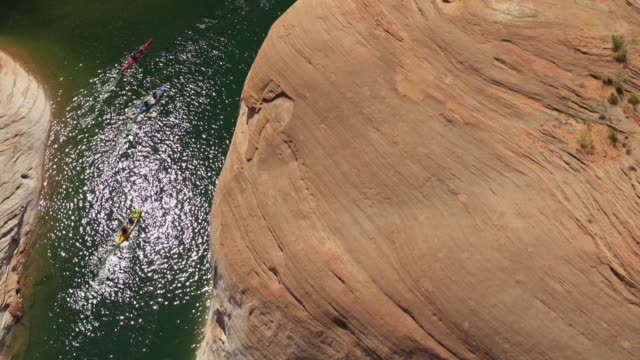 aerial high angle view of distant people paddling kayaks in remote lake / glen canyon, arizona, united states - lago powell video stock e b–roll