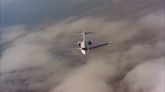 aerial high angle wide shot private jet in flight above cloud layer - private jet stock videos & royalty-free footage