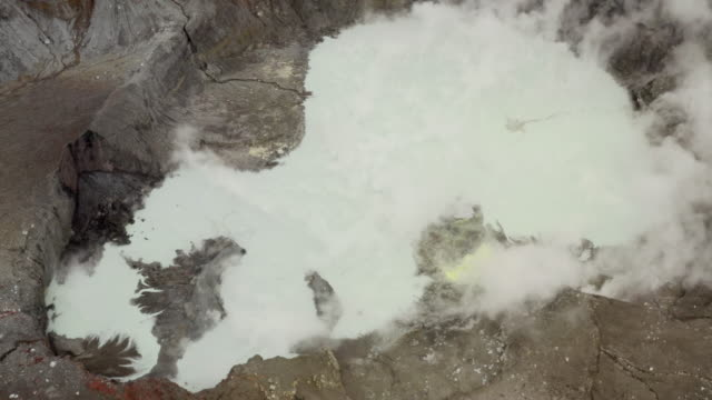 aerial: high crater of dormant volcano surrounded by mist and clouds - panning stock videos & royalty-free footage
