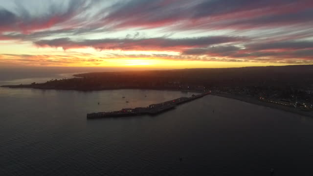 aerial high long pan: santa cruz wharf to boardwalk at sunset - santa cruz california stock videos and b-roll footage