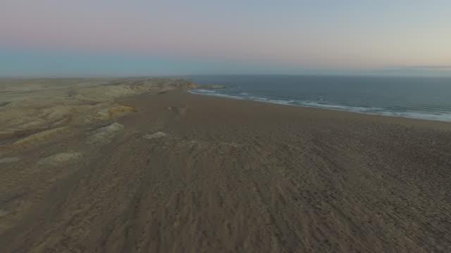 aerial high over beach, coastline, tufty hillocks, distant cliffs, sunset, namibia, 2015 - fußabdruck stock-videos und b-roll-filmmaterial
