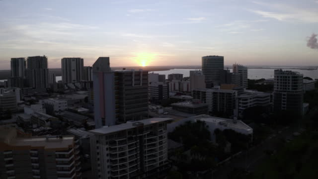 aerial: high rise buildings near water with the sun setting - darwin, australia - downtown stock videos & royalty-free footage