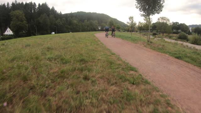森と川の近くでマウンテンバイクの空中高速ドローンショット - サイクリングロード点の映像素材/bロール
