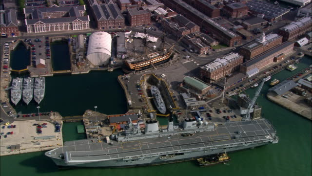 Aerial HMS Victoy and aircraft carrier at naval base/ Portsmouth, England
