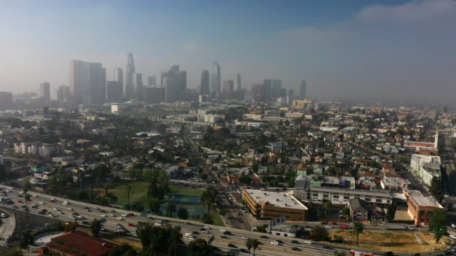 aerial: hollywood freeway and downtown la on hazy afternoon - los angeles, california - los angeles county stock-videos und b-roll-filmmaterial