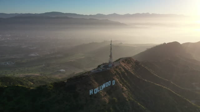 vidéos et rushes de aerial: hollywood sign, santa monica mountain range, and north hollywood at sunset  - hollywood, california - hollywood california