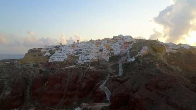 aerial: homes on the side of a bluff in santorini, greece - santorini stock videos & royalty-free footage