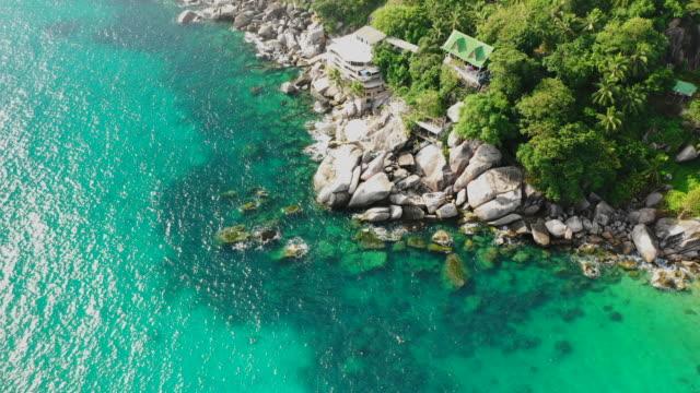 vidéos et rushes de aerial: homes sitting on boulders along a tropical ocean on a island in thailand - ko tao, thailand - île