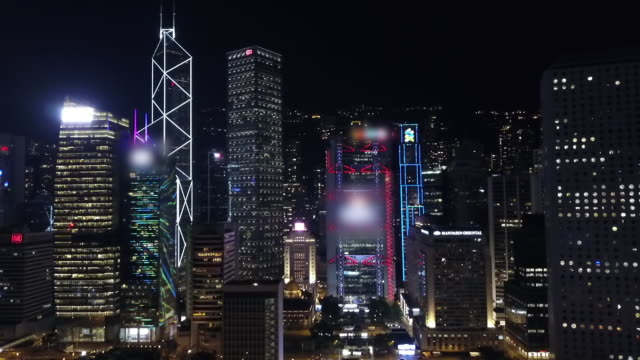 aerial: hong kong city streets and skyscrapers lit up at night - bank of china tower hong kong stock videos & royalty-free footage