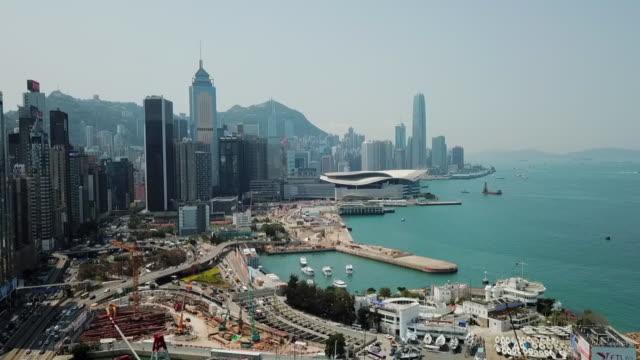 aerial: hong kong skyline, motorway, waterfront and harbor - central plaza hong kong stock videos & royalty-free footage