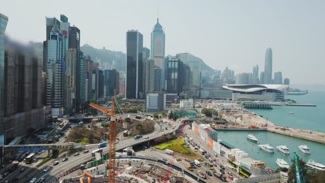 vídeos de stock e filmes b-roll de aerial: hong kong waterfront construction with skyline and victoria harbor - central plaza hong kong