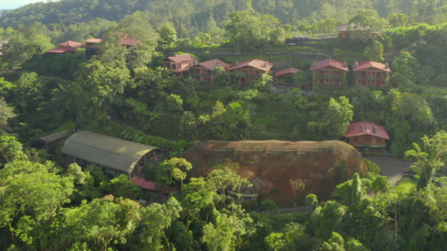 stockvideo's en b-roll-footage met aerial: houses and buildings among lush green jungle - costa rica