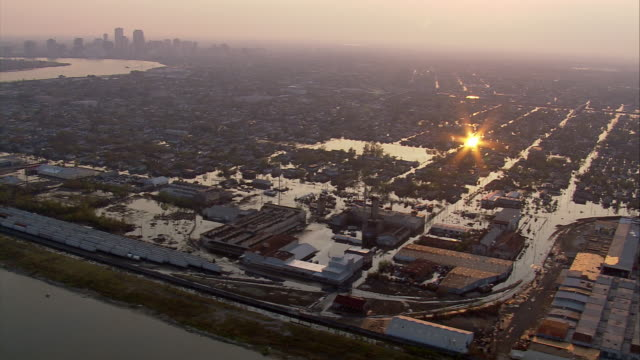 vídeos de stock, filmes e b-roll de aerial houses submerged in water in chalmette with downtown new orleans in background / sunset / louisiana - 2005