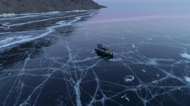 Aerial: Hovercraft moving on icy Lake Baikal at dusk