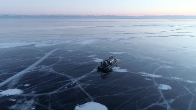 aerial: hovercraft moving on lake baikal during dusk - hovercraft stock videos & royalty-free footage