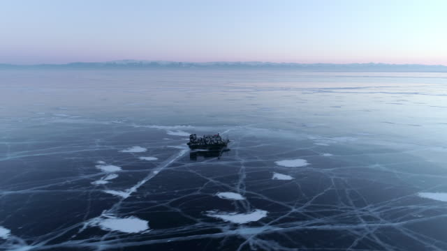 Aerial: Hovercraft on icy Lake Baikal at dusk