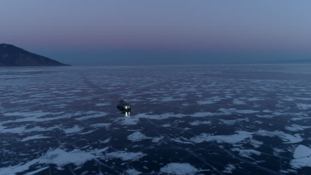 aerial: hovercraft travels on icy lake baikal against sky at dusk - hovercraft stock videos & royalty-free footage