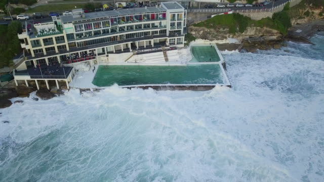 vídeos de stock, filmes e b-roll de aerial: huge waves break over luxurious pool right by the ocean, bondi beach, australia - grande angular