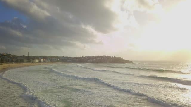 vídeos de stock, filmes e b-roll de aerial: huge waves crashing on beautiful beach, bondi beach, australia - praia de bondi