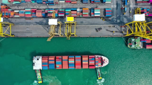aerial hyper lapse of container ship in to the port at southeast asia - cargo container stock videos & royalty-free footage